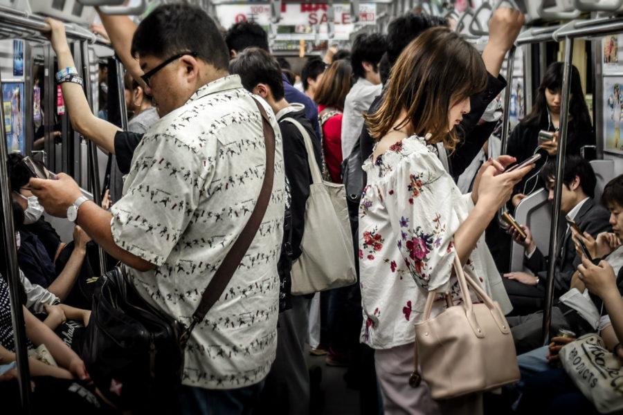 People in metro looking at phone